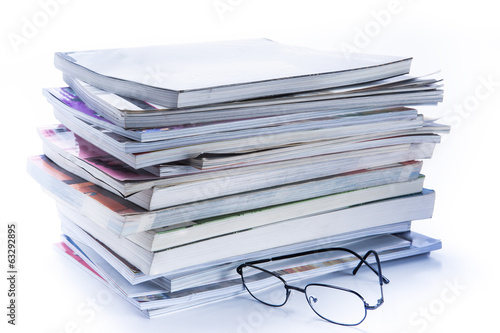 magazine and book stack with glasses