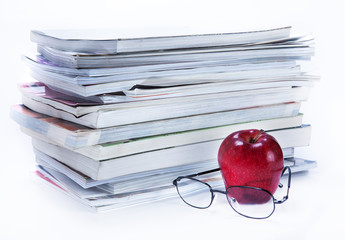 magazine and book stack with glasses and apple