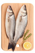 Fresh sea bass fish on wooden kitchen board.