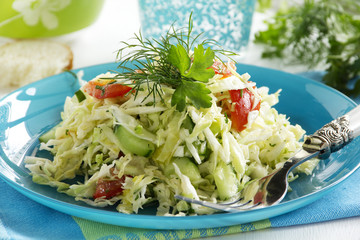 Young cabbage salad with cucumbers and tomatoes.