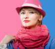 Portrait of blonde woman in a hat, pink and blue background