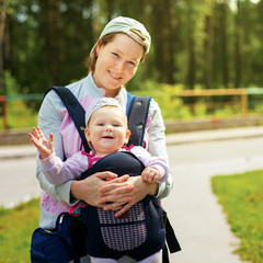 little cute girl in sling. Mother`s hand hold her. Summer time