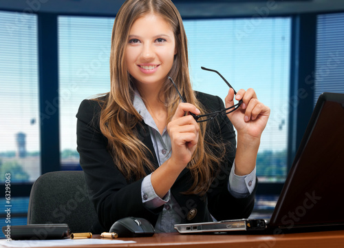 Smiling businesswoman holding her glasses