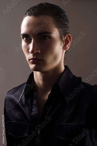 Portrait of a beautiful young man dressed in a black shirt