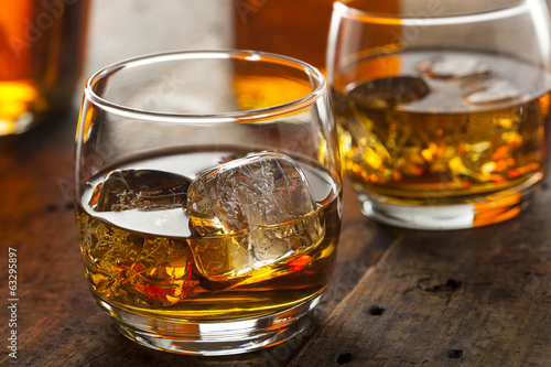 Alcoholic Whiskey Bourbon in a Glass with Ice - 63295897