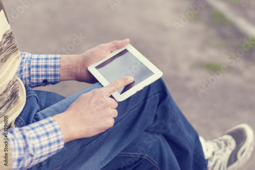 Man with tablet in hand on the street.