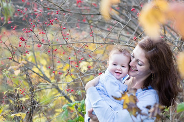 Happy young mother hugging her baby under an ashberry bush