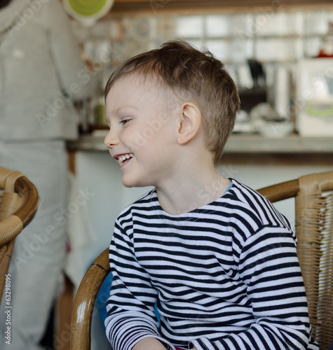 Little boy sitting laughing