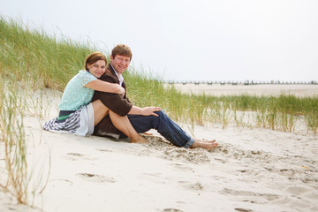 Young happy couple in love having fun on sand dunes of the beach