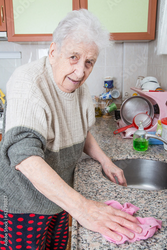 Senior Woman Cleaning Kitchen Worktop