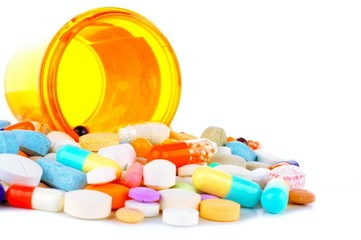Pill bottle with spilling medications over white