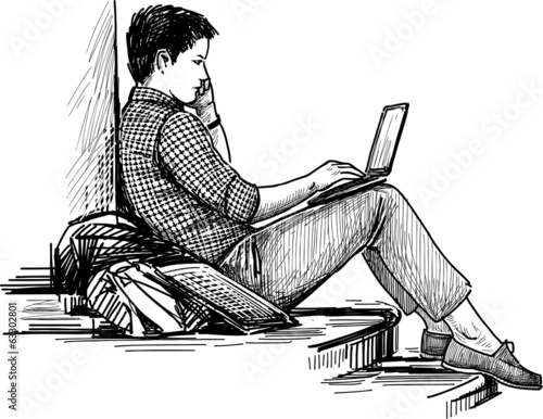 young man with laptop in the park