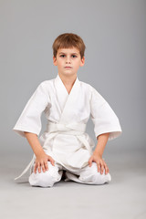 Karate boy in white kimono is sitting