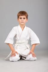 Karate boy in white kimono is sitting