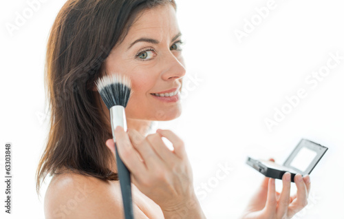 attractive woman in her forties applying makeup