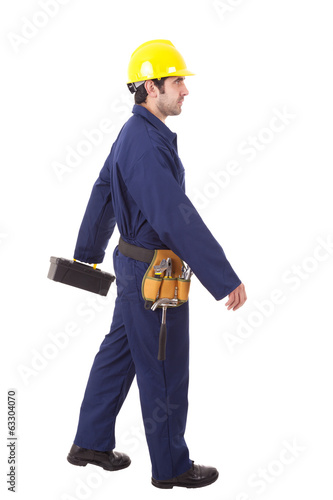 Young worker walking with a toolbox, isolated on white