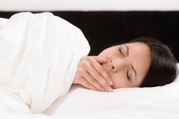 Junge Frau liegt im Bett und gähnt