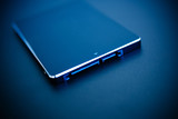 SSD disk drive in blue technological background - tilt-shift poster