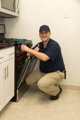 Handyman repairs oven