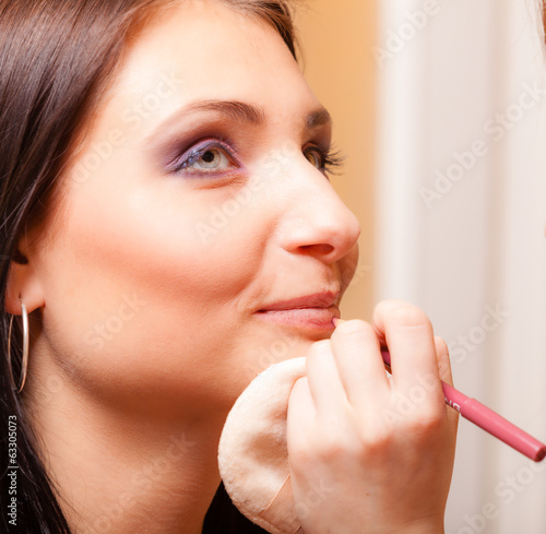 Makeup artist applying with pencil cosmetic on lips of woman