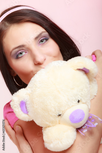 Childish woman infantile girl in pink kissing teddy bear