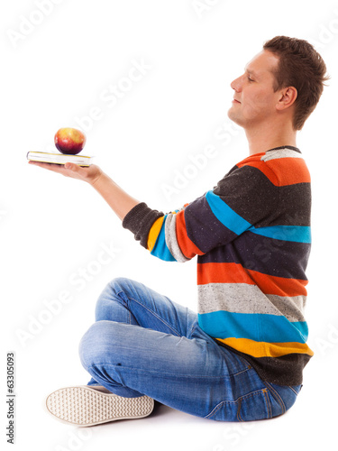 Man holding book and red apple. Healthy mind and body