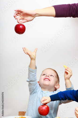 Happy childhood. Boy child kid reaching for apple fruit.