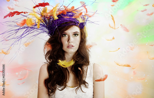 Beautiful brunette girl over feathers.