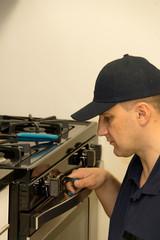 Handyman repairs stove