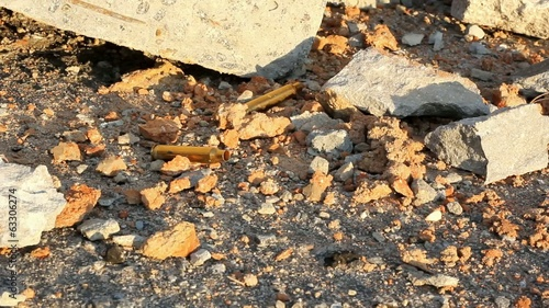 Empty Shell Casings Fall Beside Rocks