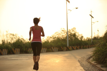fitness young asian woman running mountain road