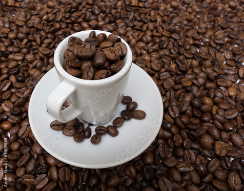 Cup with coffee beans on the background of the coffee beans