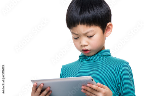 Asian little boy watching ona tablet