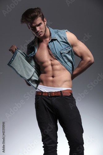 young man pulls his jeans vest