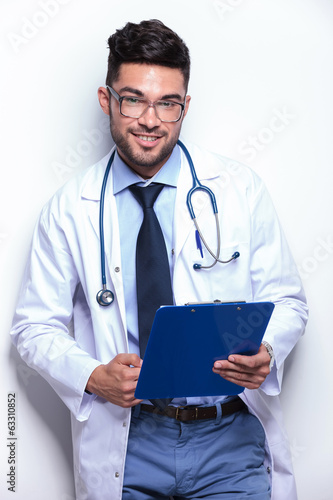 young doctor smiles with clipboard in hand