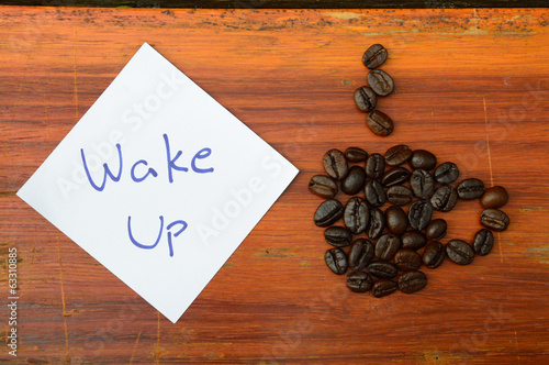 coffee beans and wake up note on the wooden background