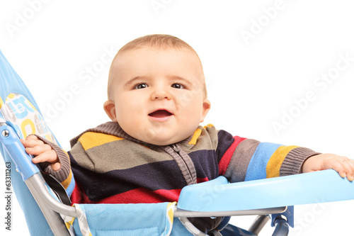 Little boy sitting in a baby stroller