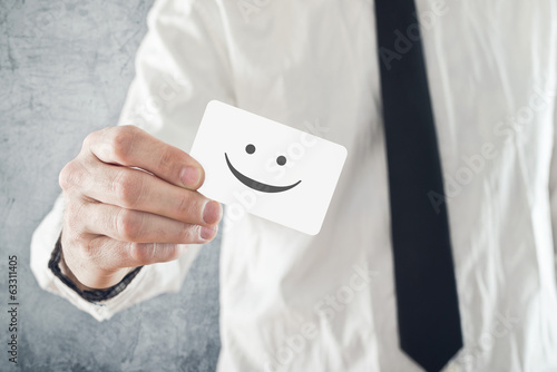 Businessman holding business card with smiley face