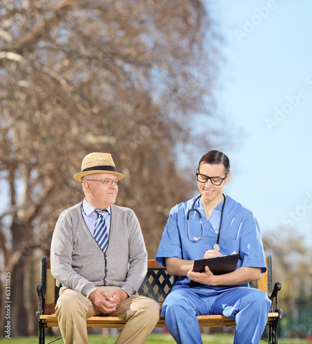 Doctor with clipboard and senior sitting in park