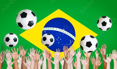 Raised Arms and Brazilian Flag as a Background for World Cup