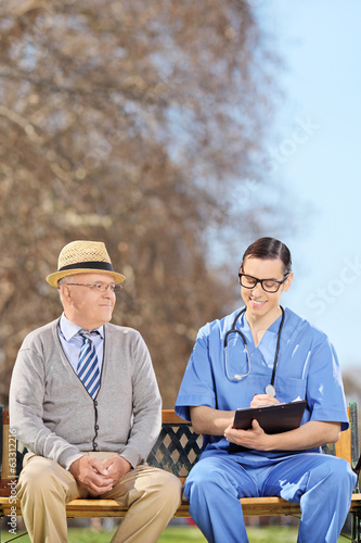 Healthcare professional doing a medical check on a senior adult