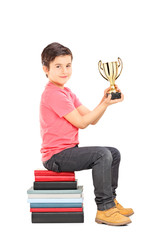Little boy holding a cup seated on stack of books