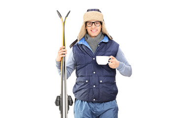 Male skier holding a cup of hot tea