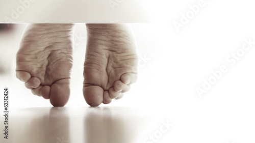 Pair of gently child's feet on the laminate flooring