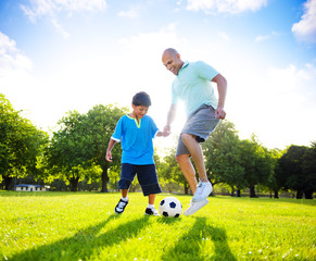 Little Boy Playing Soccer With His Father