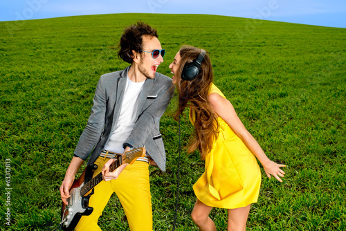 Young couple playing on guitar and enjoying the music, they shou