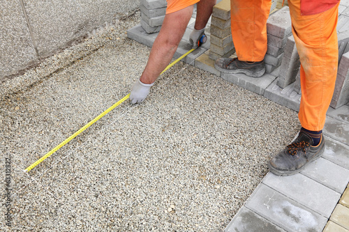 Construction worker measure foundation of brick pavement