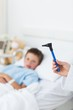 Doctor holding otoscope with boy in hospital