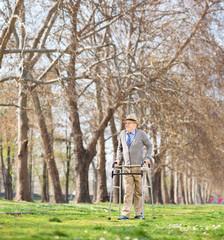 Senior man walking with walker in park