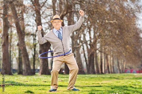 Leinwanddruck Bild Senior man, exercise with a hula hoop in park